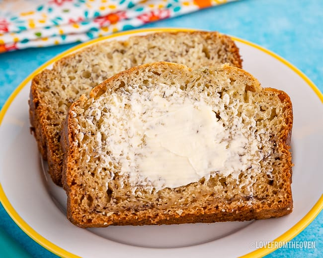 Two slices of banana bread, one with butter spread on it
