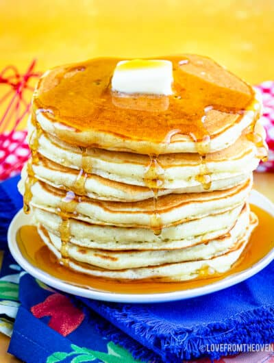 A stack of buttermilk pancakes topped with syrup and butter