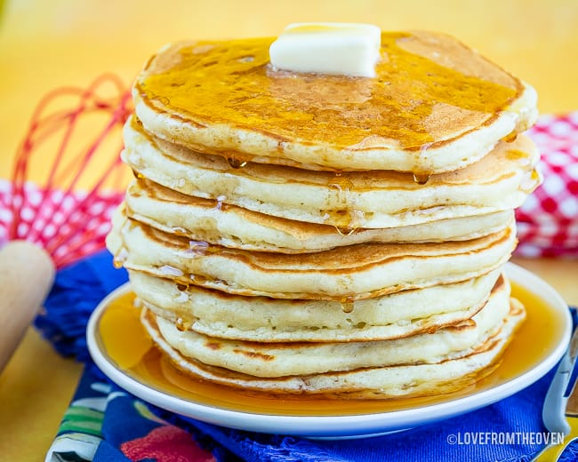 A stack of pancakes, topped with syrup and butter