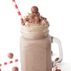 a chocolate malt milkshake with red and white straw