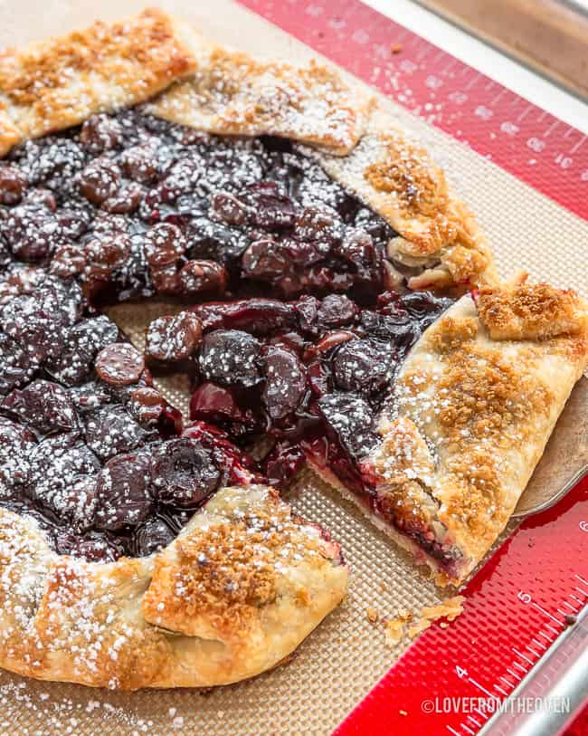 Cherry galette on a baking sheet having a piece taken out