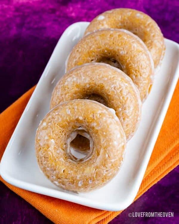 Four glazed pumpkin donuts on a tray