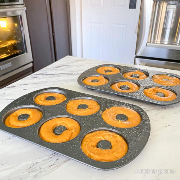 Pumpkin donut batter in pans