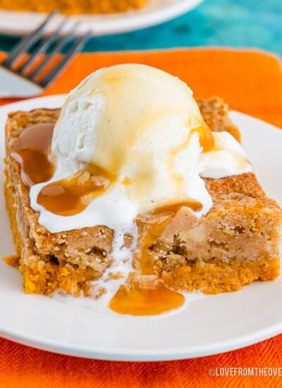 Pumpkin dump cake topped with ice cream on a white plate