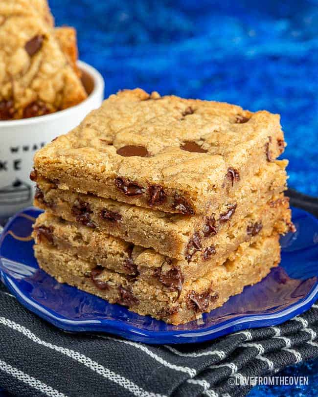 Brown butter blondies stacked on a blue plate