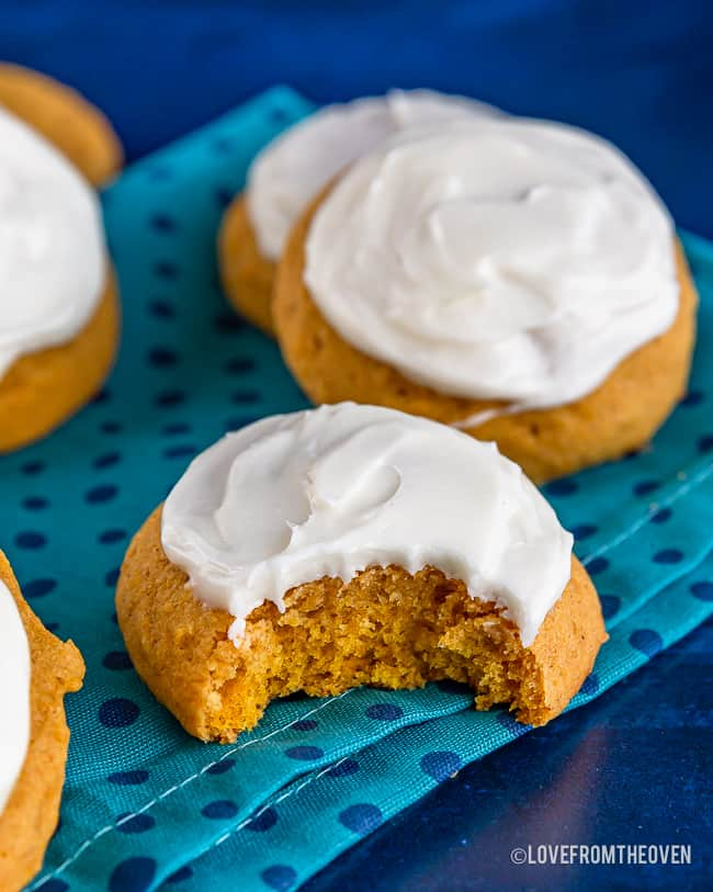 frosted pumpkin cookies, one with a bite taken out, on a blue background