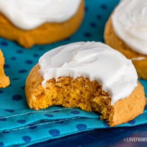 Pumpkin cookies with icing with one that has a bite taken out of it