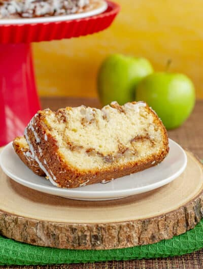 apple bread with apples and a red cake stand behind it