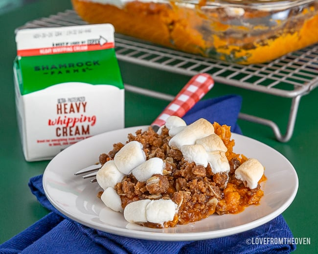 Sweet Potato Marshmallow Casserole on a plate with a carton of whipping cream next to it