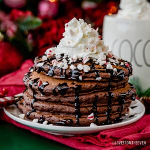 A stack of hot chocolate pancakes topped with whipped cream