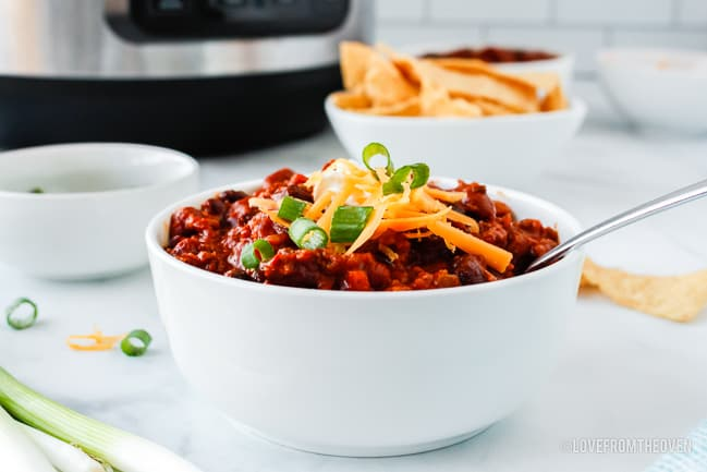 chili in a white bowl on a kitchen counter
