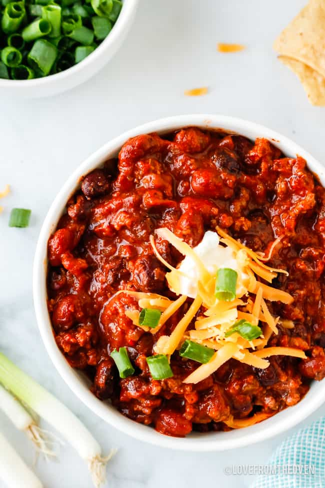 bowl of crockpot beef chili topped with sour cream and cheese