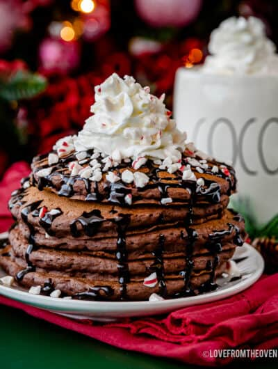 stack of hot chocolate pancakes topped with chocolate sauce and whipped cream in front of a mug of hot cocoa
