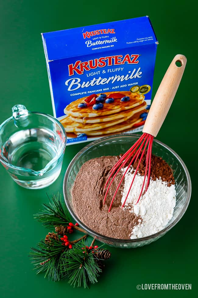 A box of Krusteaz pancake mix with a bowl of pancake ingredients