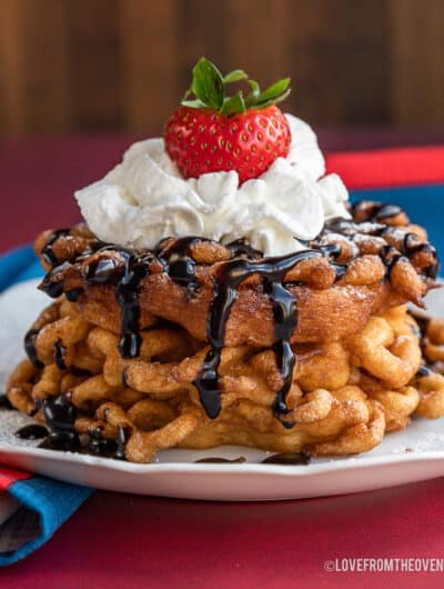 a stack of funnel cakes topped with whipped cream