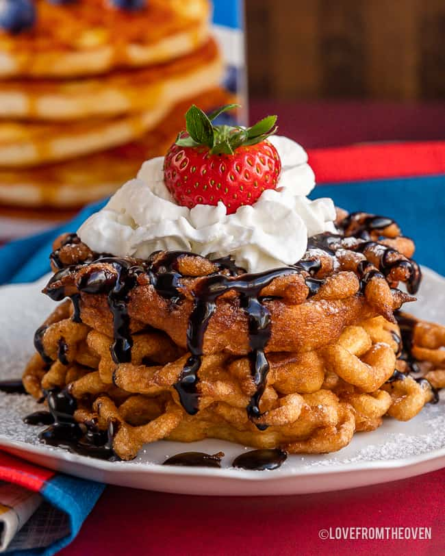 A stack of funnel cakes with chocolate sauce and whipped cream on top