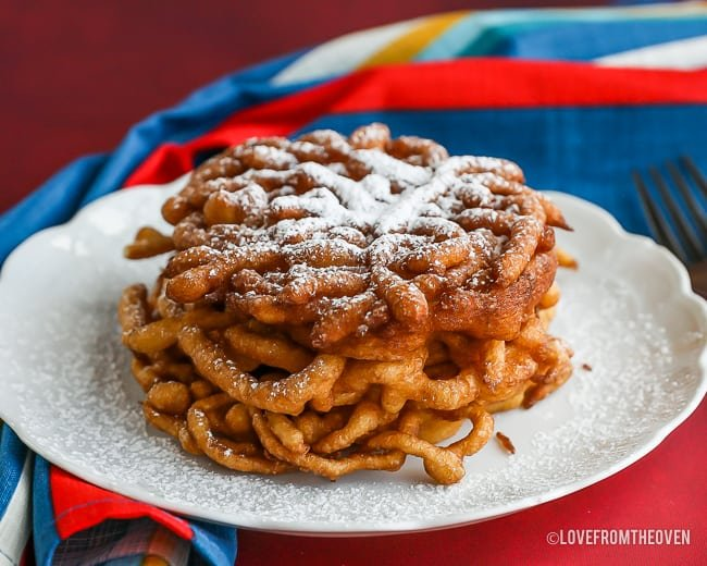 funnel cakes topped with powdered sugar on a white plate