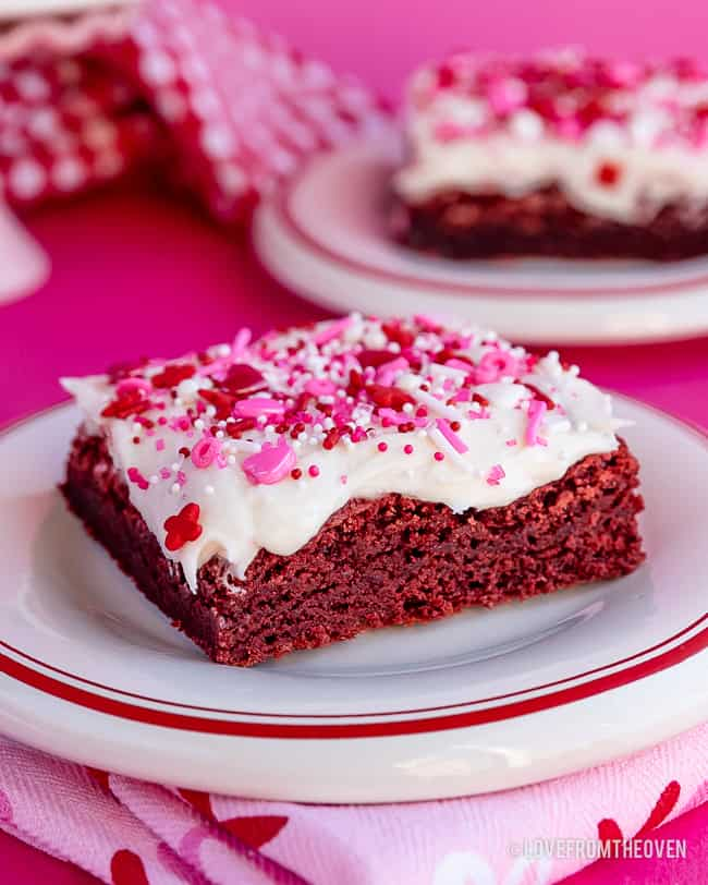 a red velvet brownie with cream cheese frosting and valentine sprinkles
