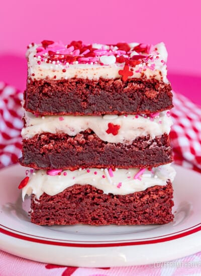 stack of red velvet brownies with frosting and pink and red sprinkles