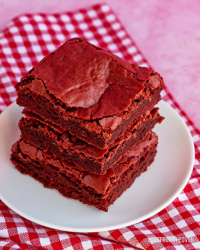 stack of red velvet brownies on a red gingham napkin