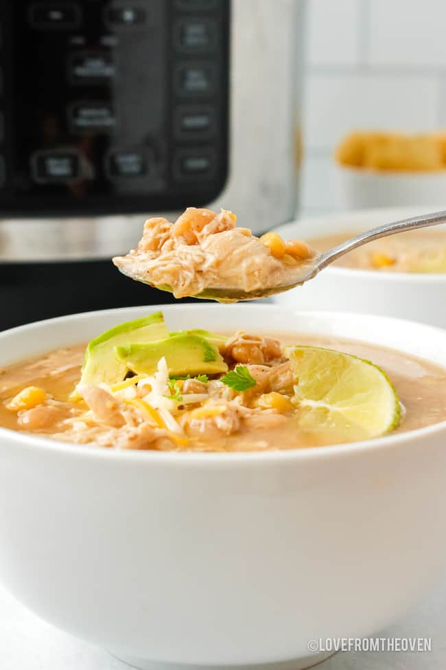 A bowl of white bean chicken chili with a spoonful being held over it