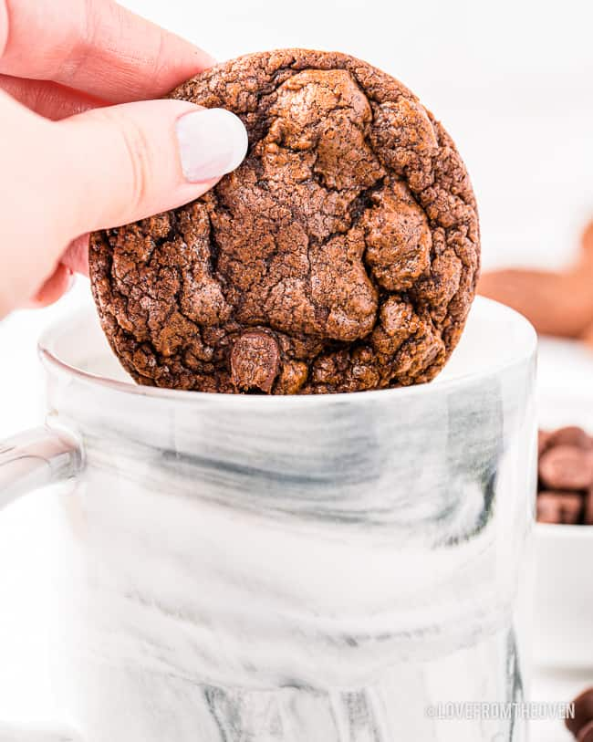 A brownie cookie being dunked into milk