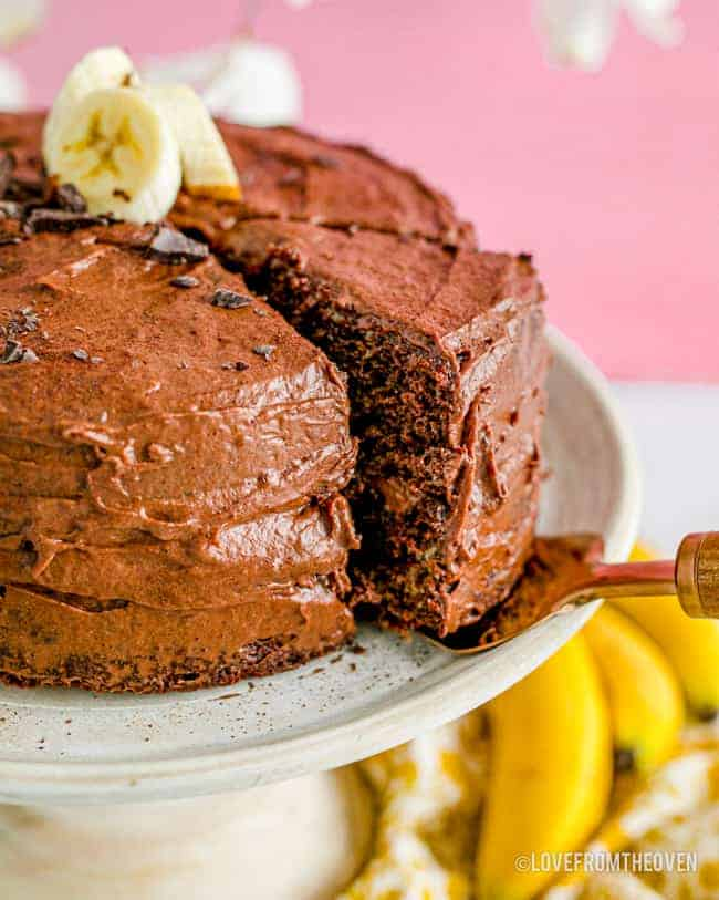 A slice of cake being taken from a chocolate banana cake