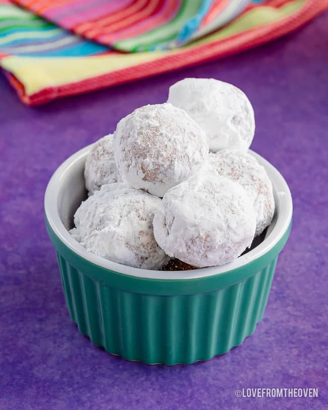 a bowl of pancake mix donut holes covered in powdered sugar