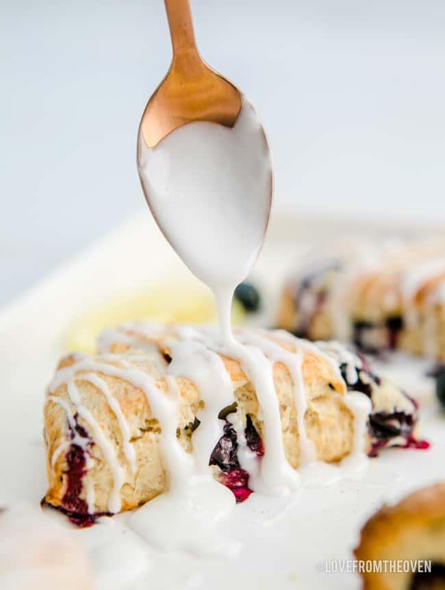a spoon putting lemon glaze on blueberry scones