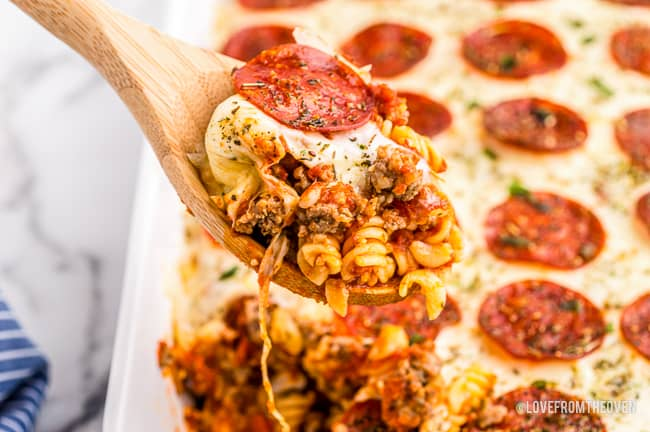 A spoon taking a serving of pizza casserole