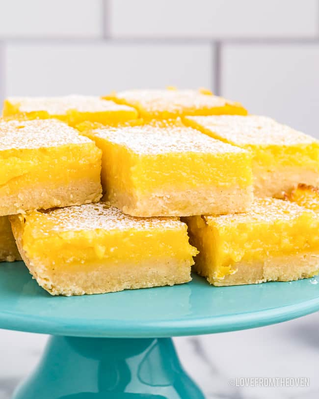 a stack of lemon bars on a blue cake stand