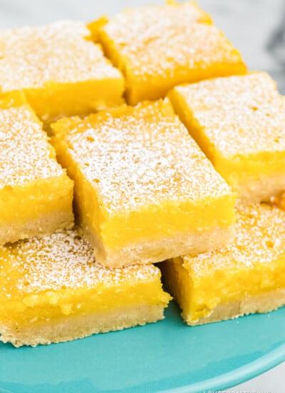 lemon bars on a blue cake plate