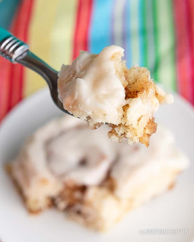 A close up of a bite of cinnamon roll on a fork