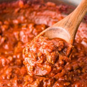A pan of homemade spaghetti sauce with a spoon stirring