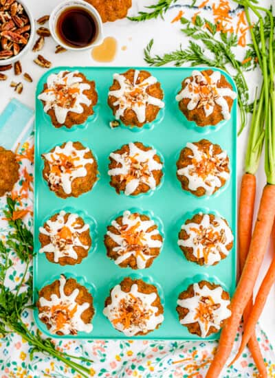 a blue pan with carrot mini bundt cakes on it, with carrots beside it