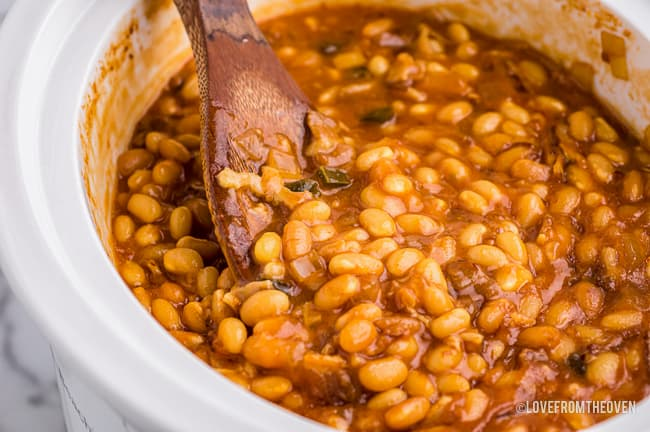 a close up of homemade baked beans in a white crockpot