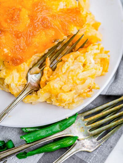 a plate of cheesy hashbrown casserole with a fork and green beans