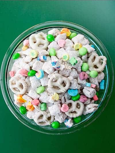 A bowl of muddy buddies on a green background