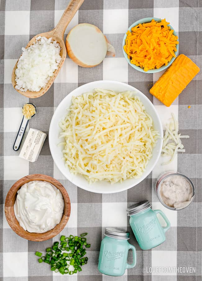 ingredients to make cheesy hashbrown casserole on a gingham background