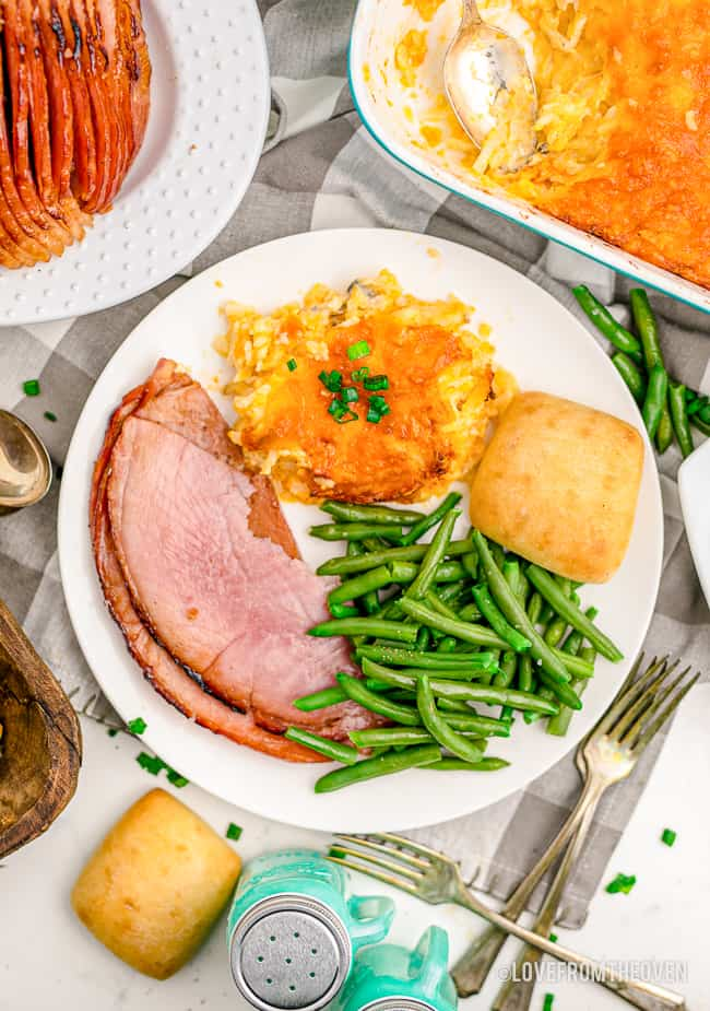 A plate full of food with green beans, ham and hashbrown casserole
