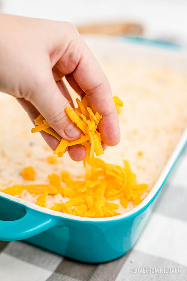 cheese being put on a potato casserole