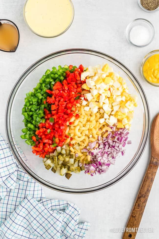 a bowl of ingredients for macaroni salad