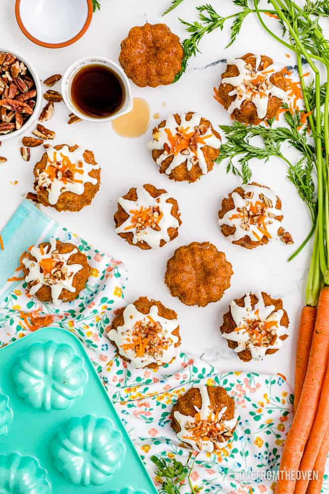 mini carrot cakes on a white background with carrots and a mint colored baking pan