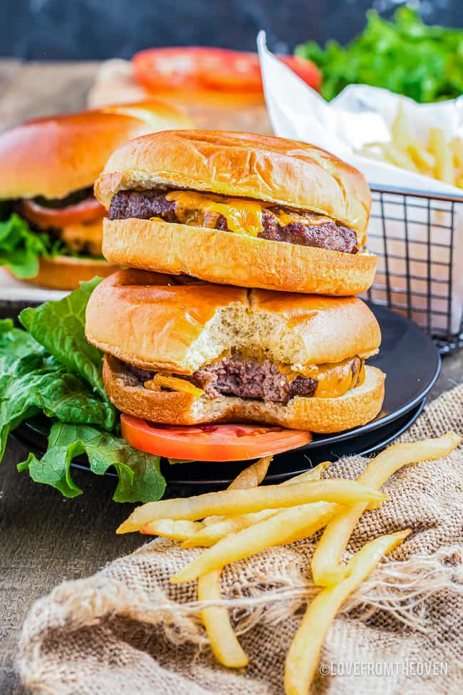 two air fryer cheeseburgers stacked and some french fries