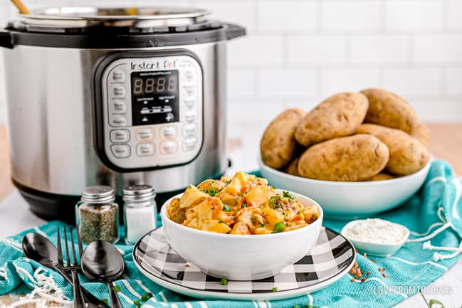 A bowl of cheesy potatoes in front of an instant pot
