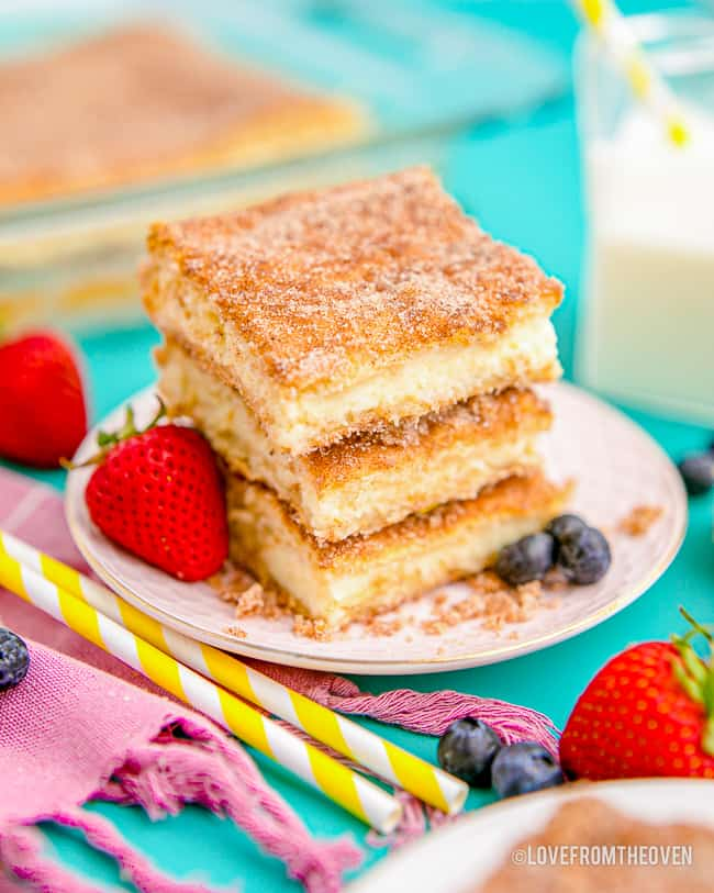 a stack of cheesecake bars topped with cinnamon and sugar