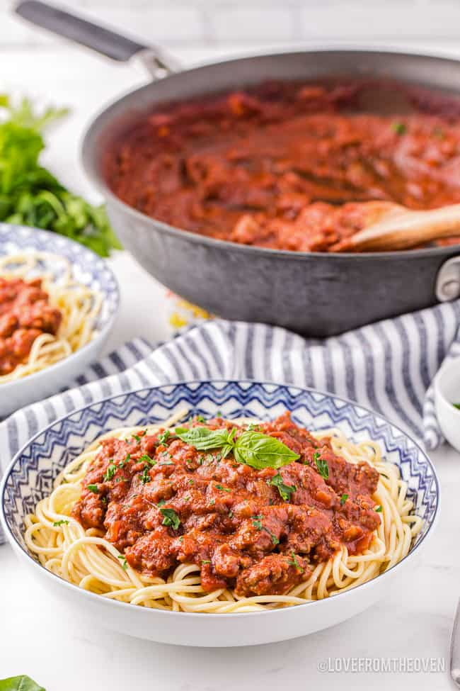 a pan of spaghetti sauce from scratch with a bowl of spaghetti