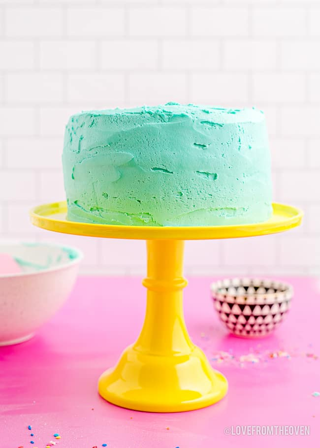 a blue frosted cake on a yellow cake stand