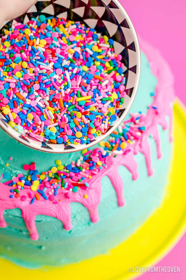sprinkles being poured on a cake