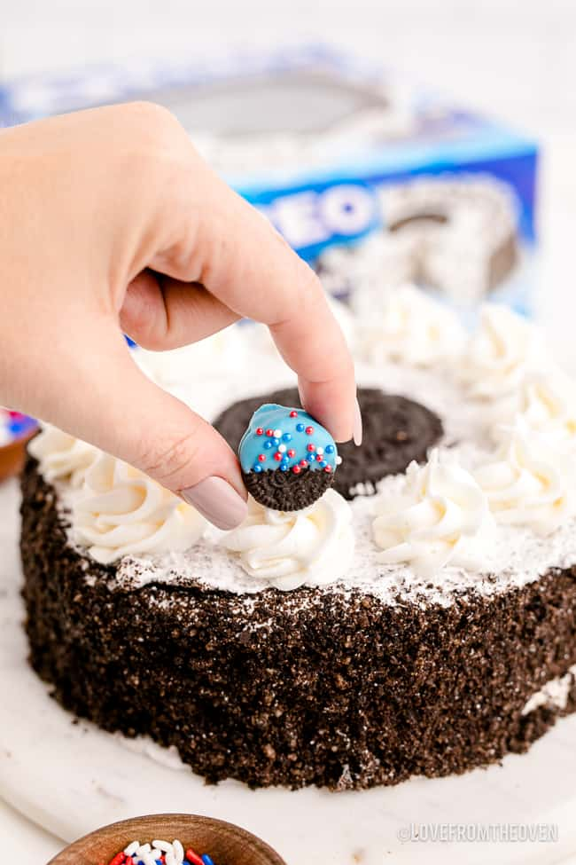 a hand decorating a store bought cake